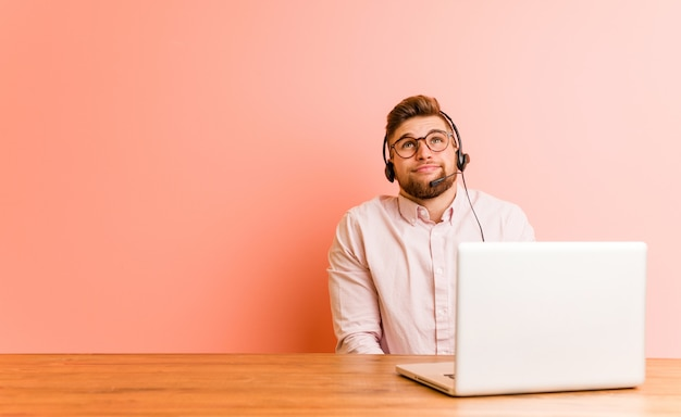 Jonge man aan het werk in een callcenter die droomt van het bereiken van doelen en doeleinden