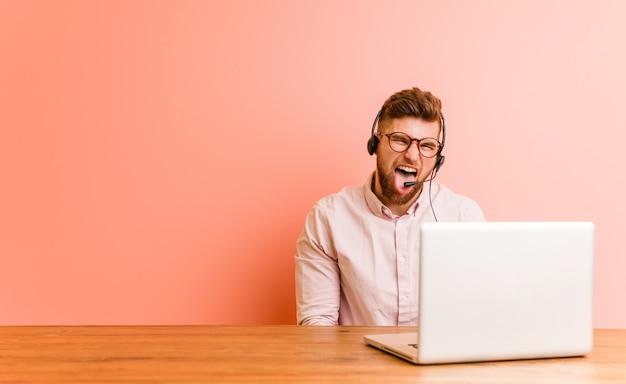 Jonge man aan het werk in een callcenter grappig en vriendelijk steekt hem tong.