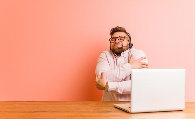Jonge man aan het werk in een callcenter knuffelt zichzelf, zorgeloos en gelukkig glimlachen.