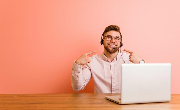 Jonge man aan het werk in een callcenter lacht, wijzende vingers op mond.