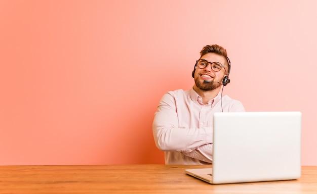 Jonge man aan het werk in een callcenter lacht zelfverzekerd met gekruiste armen.