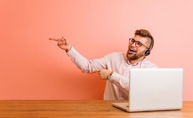 Jonge man aan het werk in een callcenter opgewonden wijzend met wijsvingers weg.