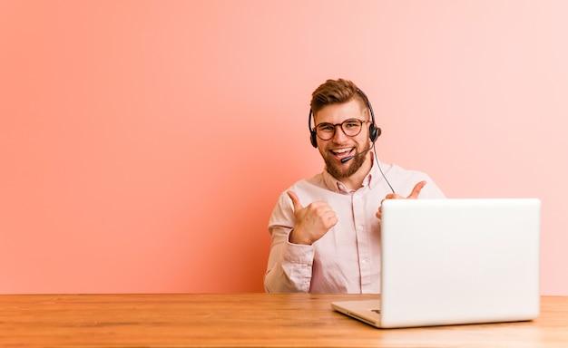Jonge man aan het werk in een callcenter verhogen beide duimen omhoog, lachend en zelfverzekerd.