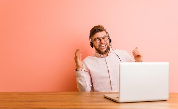 Jonge man aan het werk in een callcenter vreugdevol veel lachen. geluk concept.