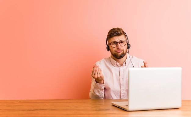 Jonge man aan het werk in een callcenter waaruit blijkt dat hij geen geld heeft.