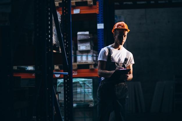 Jonge man aan het werk in een magazijn met dozen