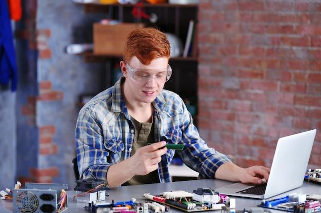 Jonge man aan het werk in reparatiecentrum