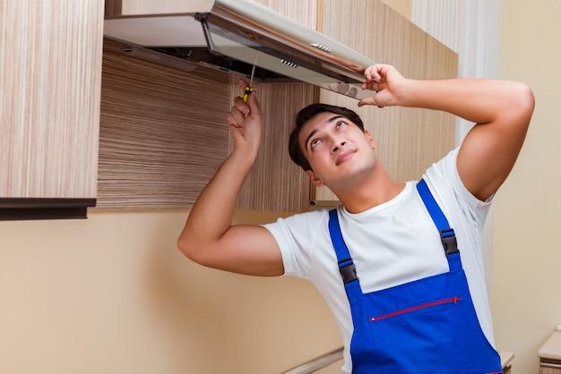 Jonge man aan het werk met keukenapparatuur
