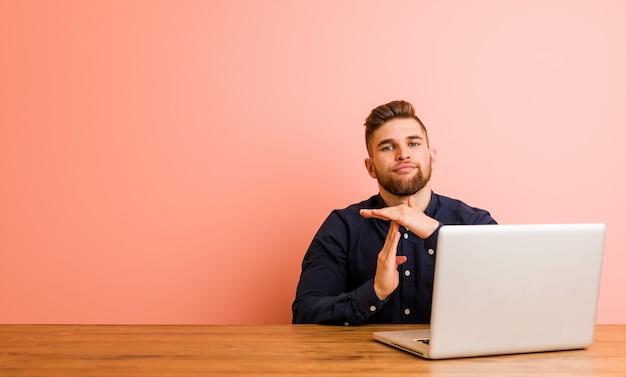 Jonge man aan het werk met zijn laptop met een time-out gebaar.