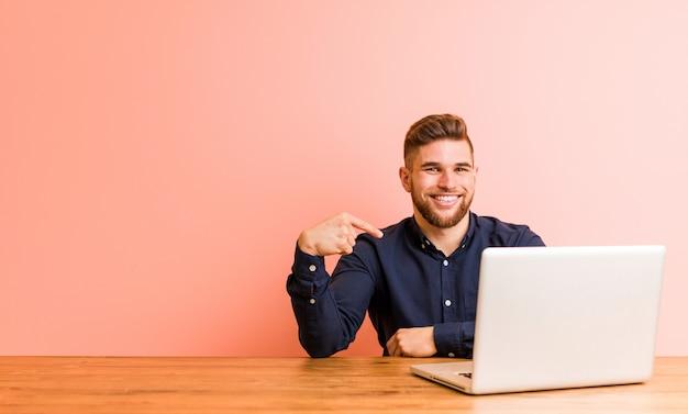 Jonge man aan het werk met zijn laptop persoon wijst zichzelf, trots en zelfverzekerd
