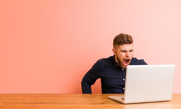 Jonge man aan het werk met zijn laptop schreeuwen erg boos en agressief.