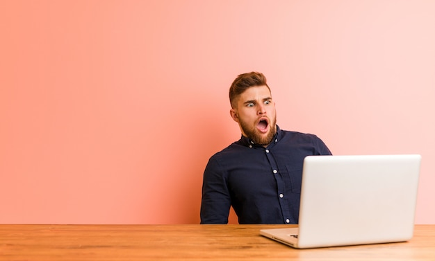 Jonge man aan het werk met zijn laptop wordt geschokt vanwege iets dat ze heeft gezien.