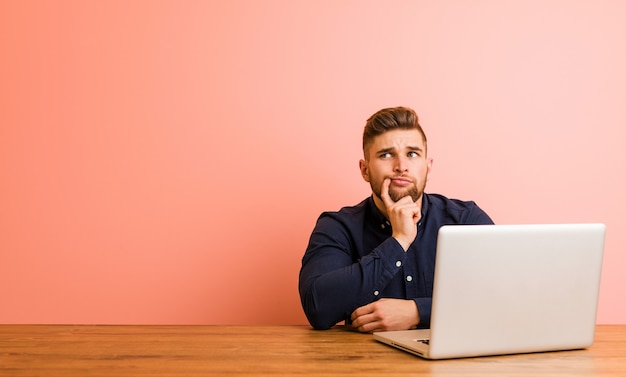 Jonge man aan het werk met zijn laptop zijwaarts op zoek met twijfelachtige en sceptische uitdrukking.