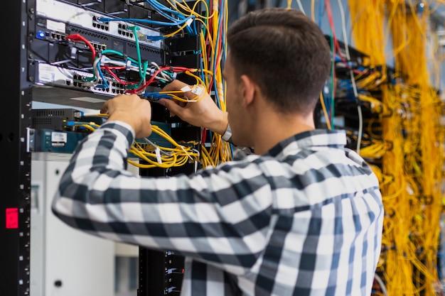Jonge man aan het werk op een ethernet-schakelaar