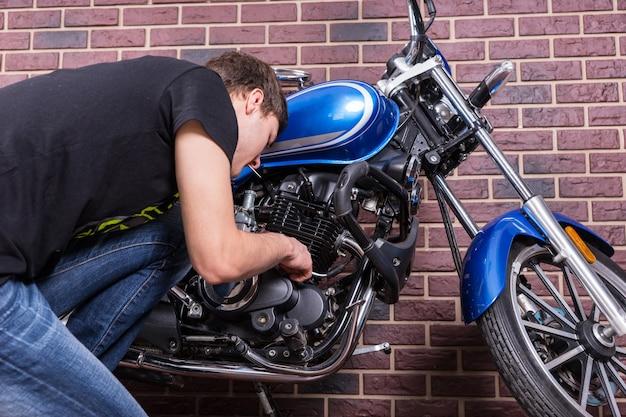Jonge man aan het werk op zijn blauwe aangepaste motorfiets terwijl hij sommige onderdelen van dichtbij bekijkt. gevangen voor huis bakstenen muur.