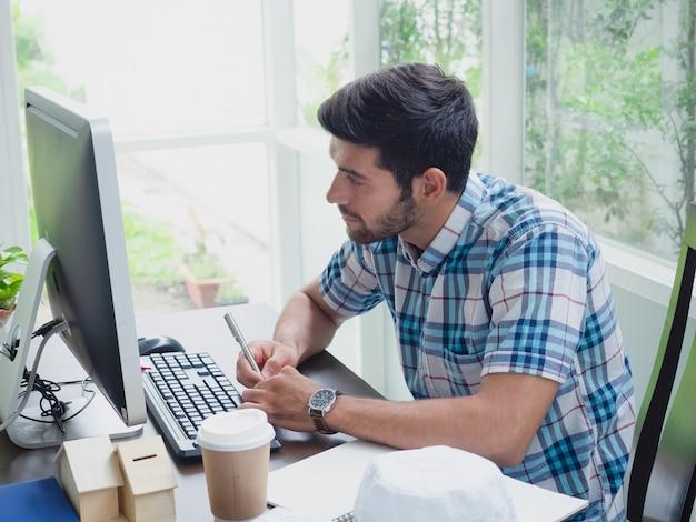 Jonge man aan het werk thuis met koffie en krant