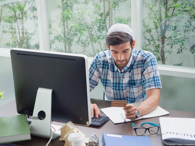 Jonge man aan het werk thuis met ziekteverzekeringskaart