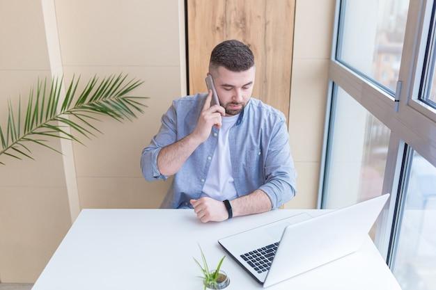 Jonge man aan het werk vanuit het kantoor zit bij het raam op de laptop gekleed in vrijetijdskleding