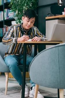Jonge man aan tafel in coworking center glimlachend terwijl hij aantekeningen maakt