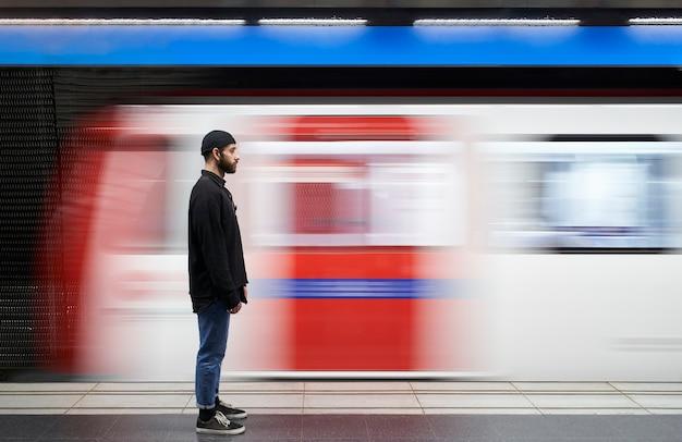Jonge man aan zijn zijde met een masker op het metroplatform