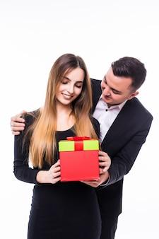 Jonge man aanwezig cadeau aan zijn vriendin vrouw in rode doos op wit