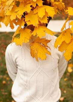 Jonge man achter herfstbladeren