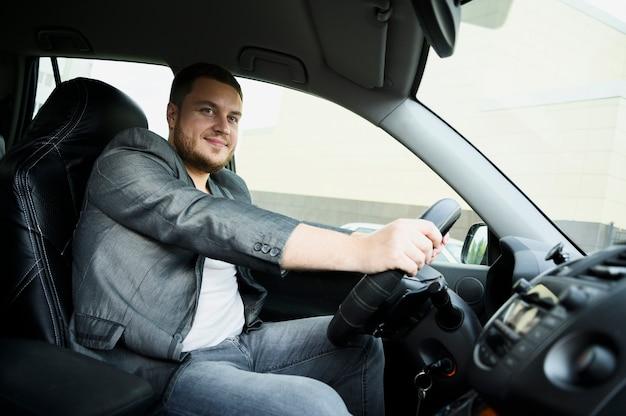 Jonge man achter het stuur kijken naar de camera