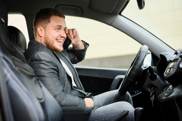 Jonge man achter het stuur met zijn telefoon op zijn oor