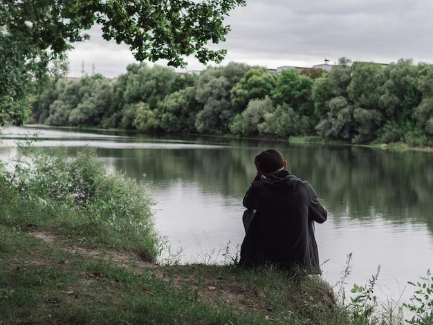 Jonge man achteraanzicht. ga bij bewolkt weer op de oever van de rivier zitten. eenzaamheid