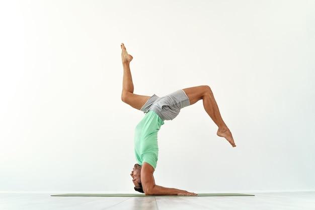 Jonge man acrobatiek gymnastiek doet een handstand studio geïsoleerd op witte atletische sportman