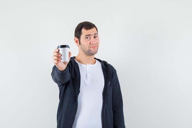 Jonge man afhaalmaaltijden koffiekopje tonen aan camera in wit t-shirt en zip-front zwarte hoodie en op zoek optimistisch, vooraanzicht.