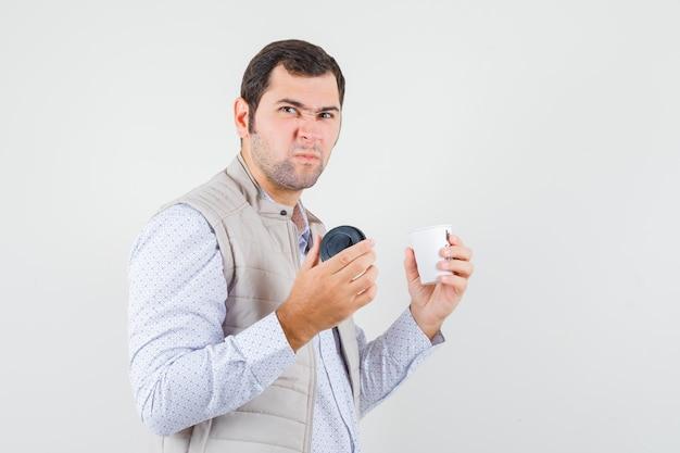 Jonge man afhaalmaaltijden kopje koffie houden en openen in beige jas en op zoek ontevreden, vooraanzicht.