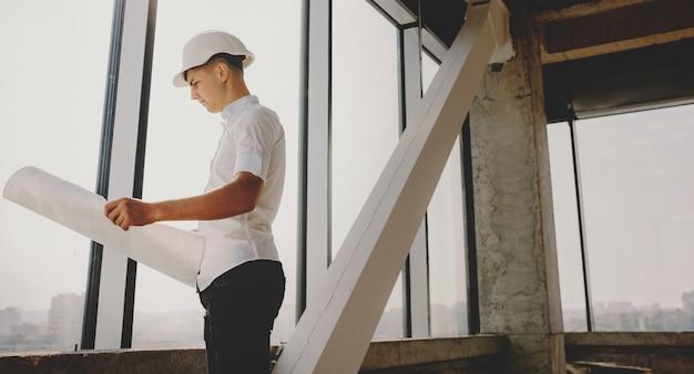 Jonge man analyseert de kaart van het gebouw terwijl hij een helm draagt