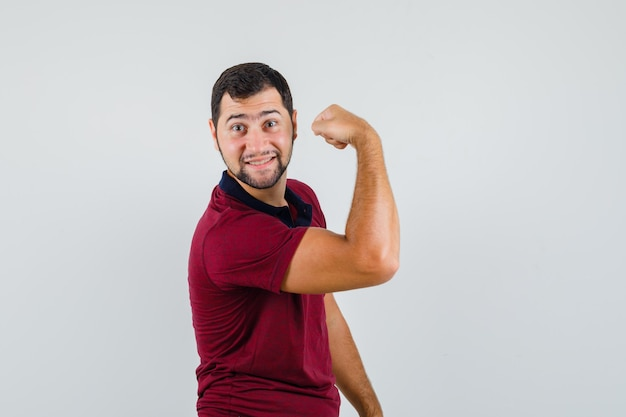 Jonge man arm spier in rood t-shirt tonen en op zoek flexibel, vooraanzicht.
