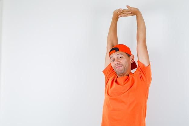 Jonge man armen in oranje t-shirt en pet strekken en op zoek ontspannen