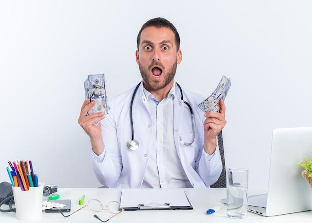 Jonge man arts in witte jas en met een stethoscoop die contant geld vasthoudt en er verbaasd en verrast uitziet terwijl hij aan de tafel zit met een laptop op een witte achtergrond