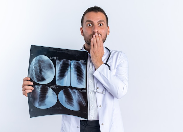 Jonge man arts in witte jas en met een stethoscoop om de nek met röntgenfoto's die geschokt zijn over de mond met de hand die over de witte muur staat
