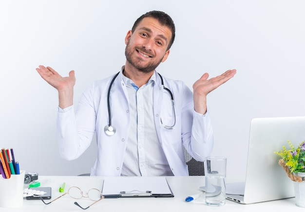 Jonge man arts in witte jas en met stethoscoop kijkend naar voren gelukkig en vrolijk glimlachend breed spreidende armen naar de zijkanten zittend aan de tafel met laptop over witte muur
