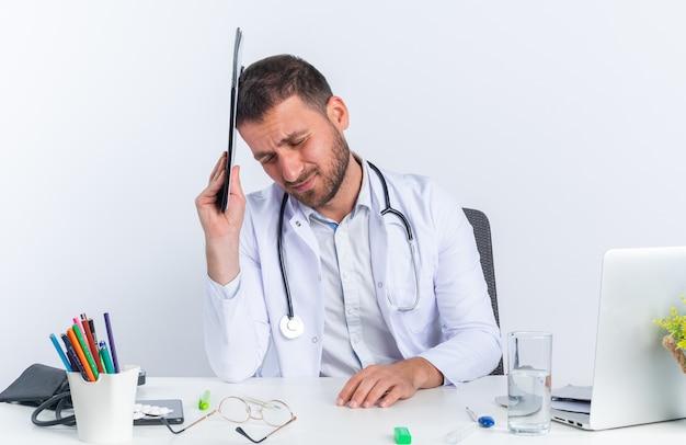Jonge man arts in witte jas en met stethoscoop met klembord boven zijn hoofd ziet er moe en overwerkt uit zittend aan de tafel met laptop over witte muur