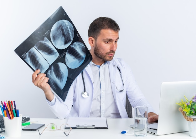 Jonge man arts in witte jas en met stethoscoop met röntgenfoto kijkend naar het scherm van zijn laptop zittend aan de tafel op wit