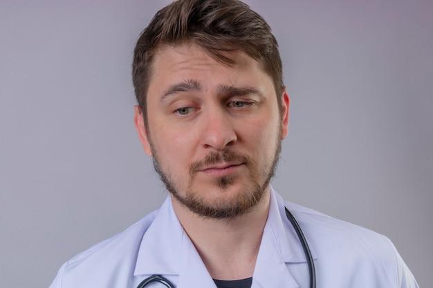 Jonge man arts witte jas dragen en stethoscoop die zeer droevig en overwerkt over witte achtergrond kijken
