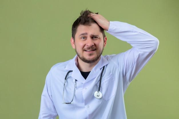 Jonge man arts witte jas dragen en stethoscoop verrast met blij gezicht over geïsoleerde groene achtergrond