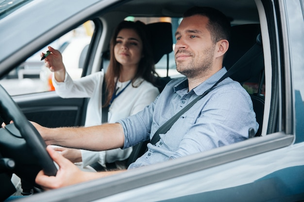 Jonge man autorijden met zijn instructeur