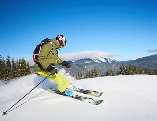 Jonge man backpacker skiën op en neer hellingen. mannelijke skiër opleiding in zonnige winterdag. backcountry skiën concept.