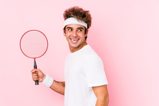 Jonge man badminton spelen geïsoleerd kijkt opzij glimlachend, vrolijk en aangenaam.