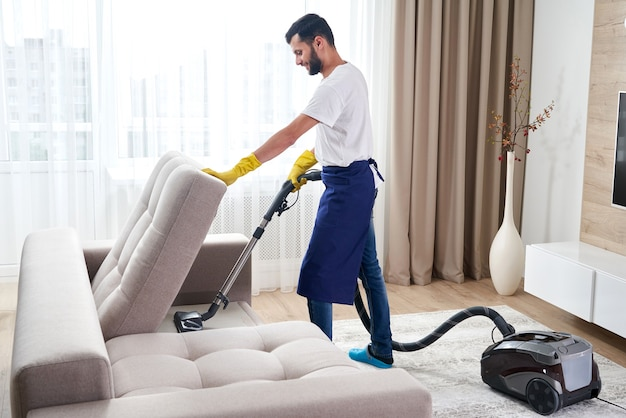 Jonge man bank met stofzuiger schoonmaken in het verlaten van kamer thuis