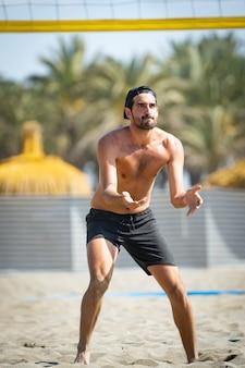 Jonge man beachvolleybal spelen op het strand op een zonnige dag