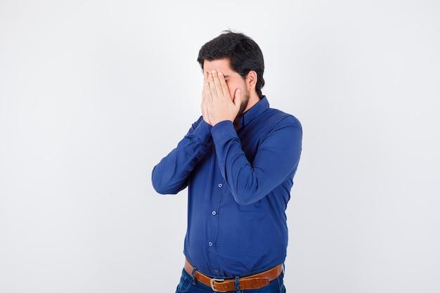 Jonge man bedekt gezicht met handen in shirt, spijkerbroek en ziet er gestrest uit. .