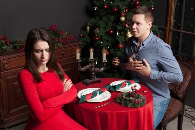 Jonge man bekent zijn liefde voor ontevreden mooie vrouw, liefdespaar in luxe restaurant.