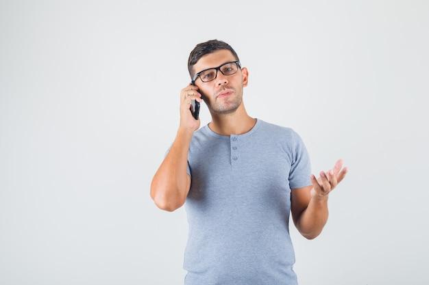 Jonge man bellen in grijs t-shirt, bril en op zoek attent